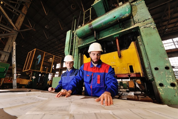 Two workers in construction helmets discuss a plan