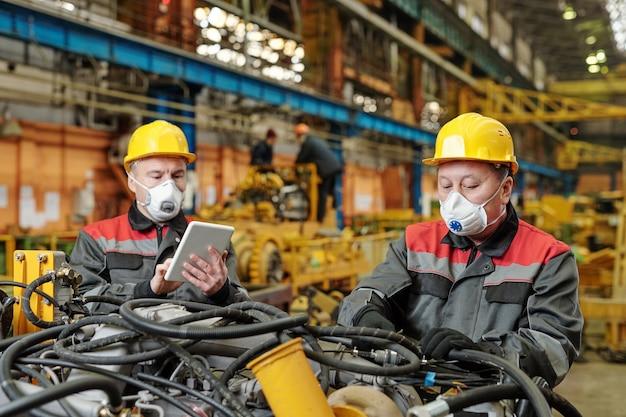마스크를 쓴 두 명의 작업자 공장에서 기계 장비와 함께 팀 작업