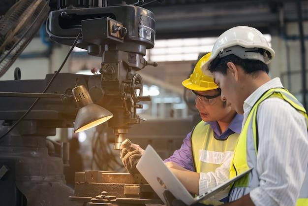 チームディスカッションとしての生産工場の2人の労働者、バックグラウンドでの産業シーン、一緒に製造活動を行う