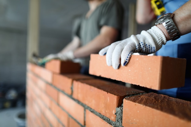 Two workers making red brick wall at construction site close-up