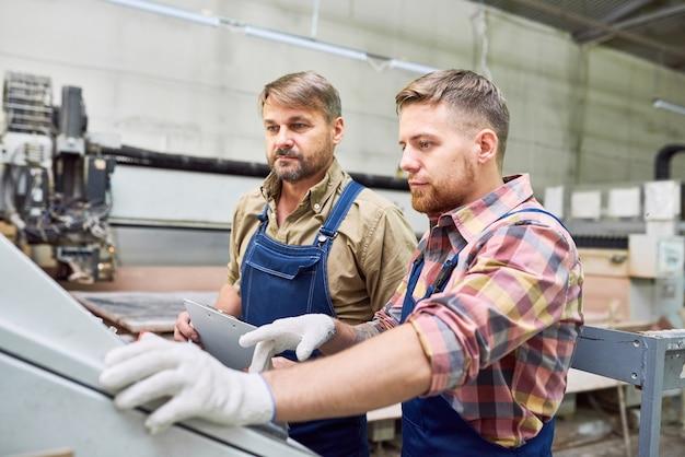 공장에서 기계를 운영하는 두 노동자