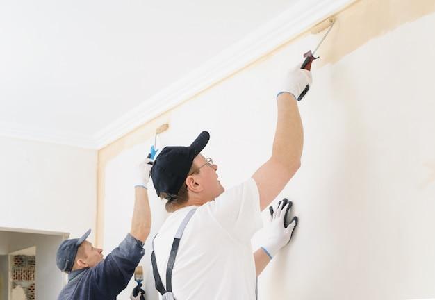 Двое рабочих красят стены в комнате.
