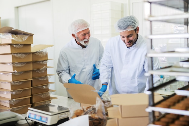 Two workers in sterile white uniforms packing cookies and talking while standing in food factory.