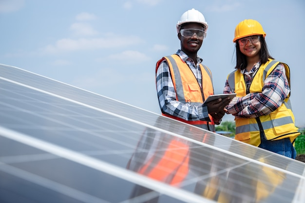 Two workers technicians installing heavy solar photo voltaic panels to high steel platform in corn field. photovoltaic module idea for clean energy. environment eco green