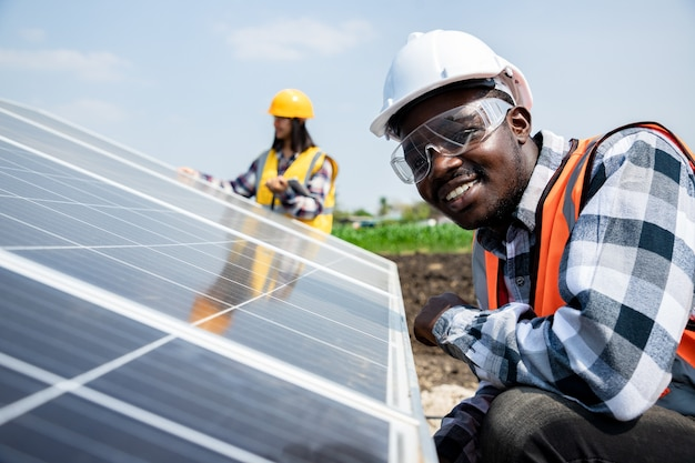 Two workers technicians installing heavy solar photo voltaic panels to high steel platform in corn field. photovoltaic module idea for clean energy. green energy concept