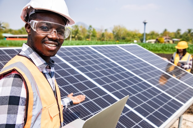 Two workers technicians installing heavy solar photo voltaic panels to high steel platform in corn field. photovoltaic module idea for clean energy