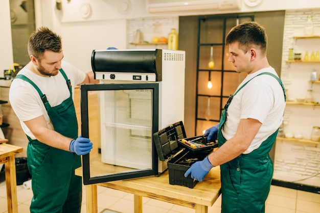 Two workers in uniform repair refrigerator at home. repairing of fridge occupation, professional service