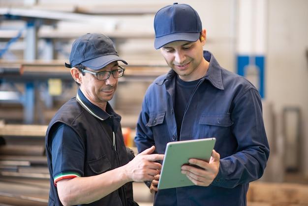Двое рабочих с помощью планшета на современном заводе