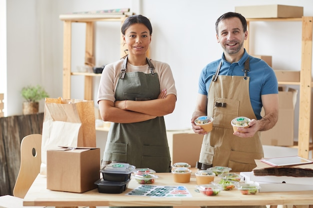 Two workers wearing aprons smiling while packaging orders at wooden table, food delivery service