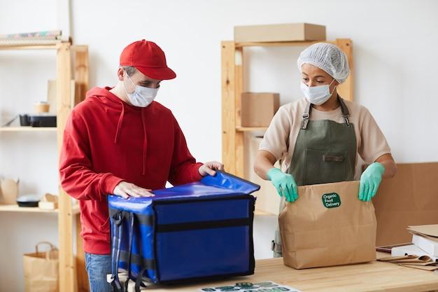 Двое рабочих в масках упаковывают заказы в службу бесконтактной доставки еды