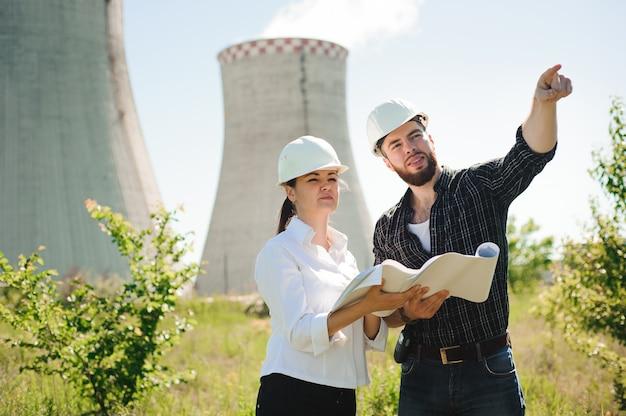 보호 헬멧을 착용하는 두 노동자는 발전소에서 작동