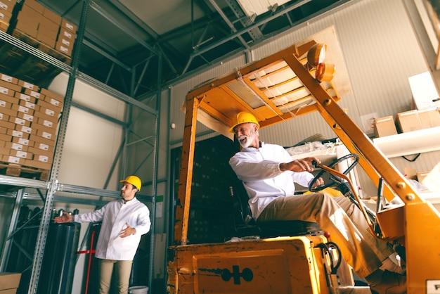 Двое рабочих с касками на голове, работающих на складе. один водительский погрузчик, а младший направляет его.