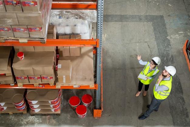 Двое рабочих склада в униформе обсуждают перед стеллажом с упакованными товарами