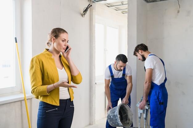 Двое рабочих готовят цемент в ведре. женщина серьезно говорит по телефону