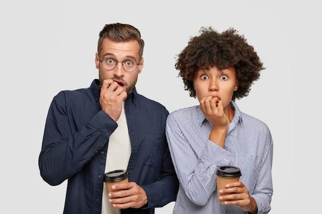 Два встревоженных студента смешанной расы кусают ногти, ждут результатов