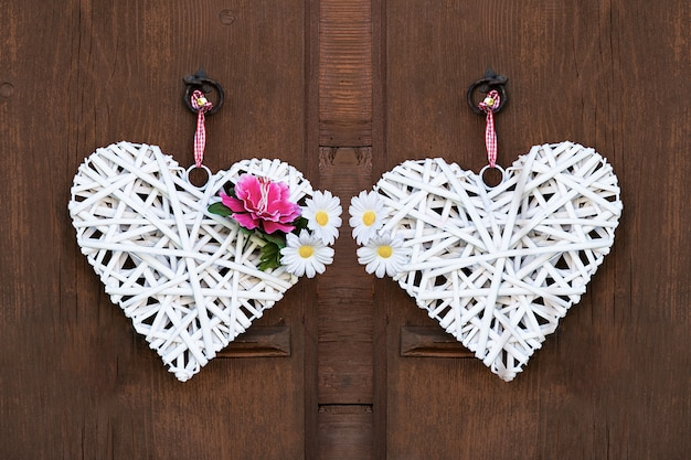 Two woven white hearts with peonies and daisies hanging on a wooden wall.