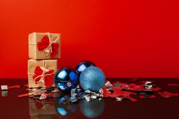 赤い背景の上のクリスマスのための2つの包まれたギフトボックス