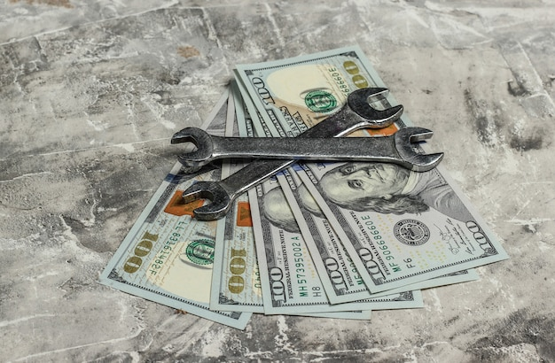 Two wrench and dollar bills on gray concrete background. work tool