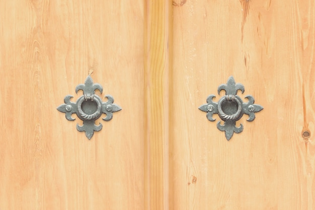 Two wrought metal rings on a wooden door. close up