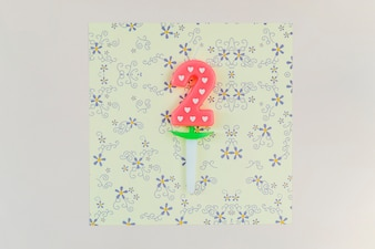 Two year candle on craft floral paper over the colored backdrop