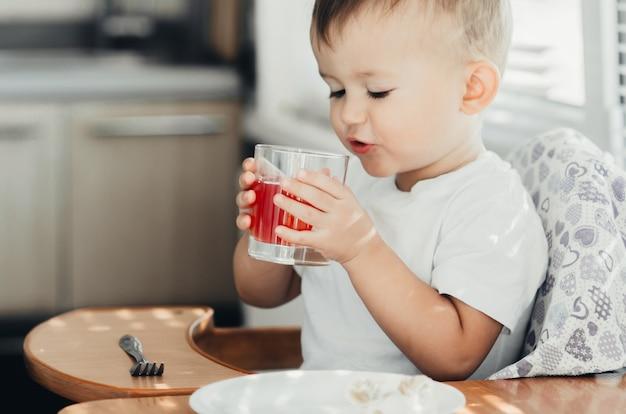 부엌에서 유리 컵으로 주스를 마시는 2세 소년