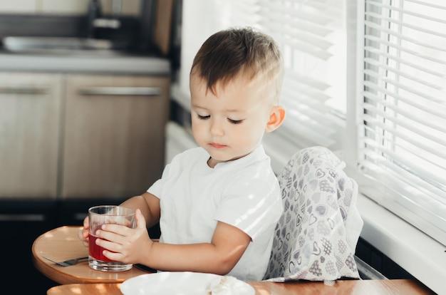 Два года мальчик пьет сок из стеклянной чашки на кухне