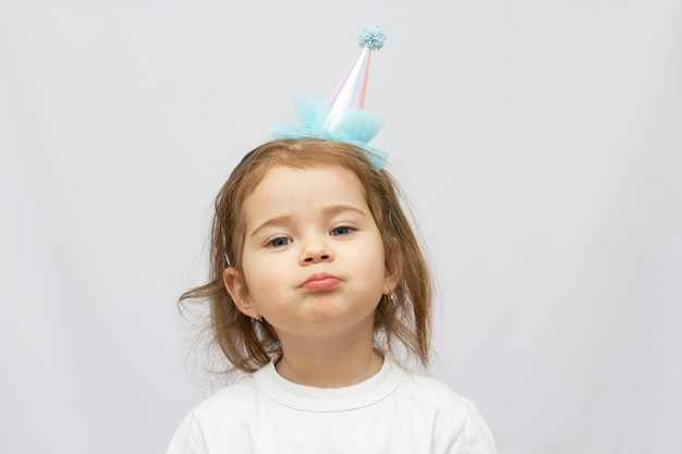 Two years old blonde child with party hat and tired face on white background