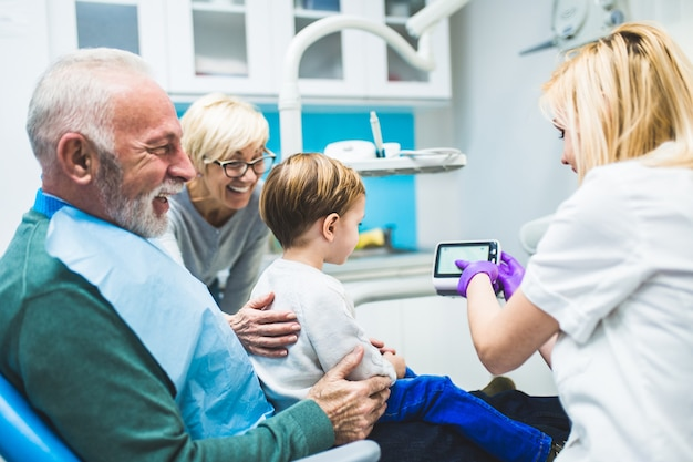 Two years old boy with his grandfather and grandmother first time on dental chair.