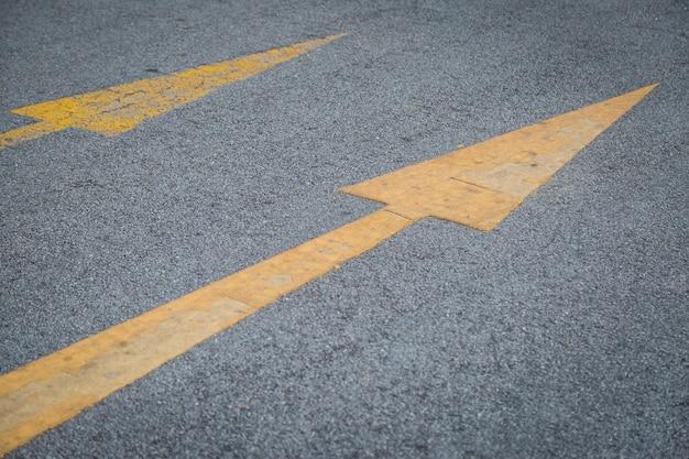 2つの黄色の矢印古いと新しい方向にアスファルト道路の背景