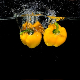 Two yellow bell peppers falling into clear water
