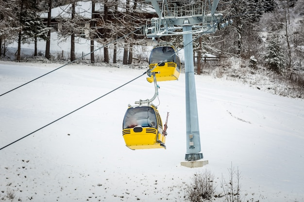 Две желтые канатные дороги на горнолыжном склоне в австрийских альпах
