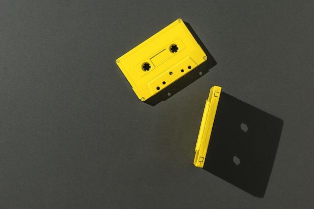 검정색 배경에 밝은 빛에 자기 테이프가 있는 두 개의 노란색 카세트. 플랫 레이.