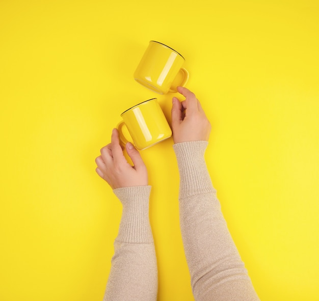 Two yellow ceramic cups are supported by a female hand