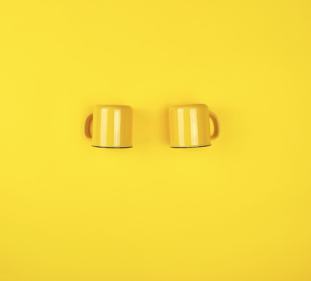 Two yellow ceramic cups with a handle on yellow