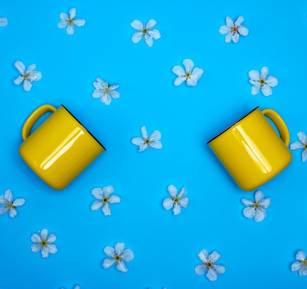 Two yellow ceramic mugs on a blue