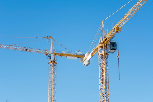 Two yellow construction cranes on blue sky background