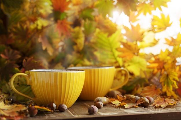Две желтые чашки чая в осенней листве с желудями и орехами. осенняя атмосфера.