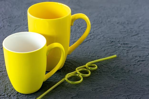 회색 배경에 두 개의 노란색 컵입니다. 2021년 올해의 컬러.