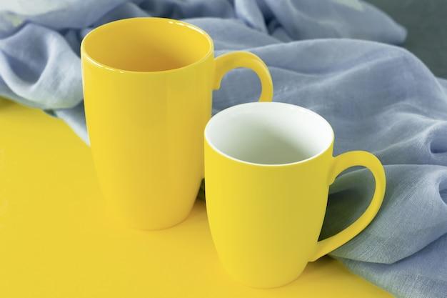 회색과 노란색 배경에 두 개의 노란색 컵입니다. 2021년 올해의 컬러.