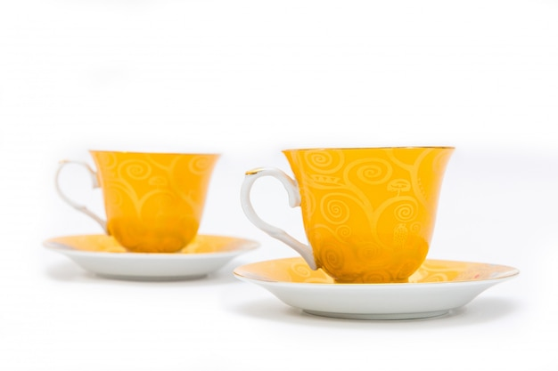 Two yellow cups of tea on whtie background. isolated on white