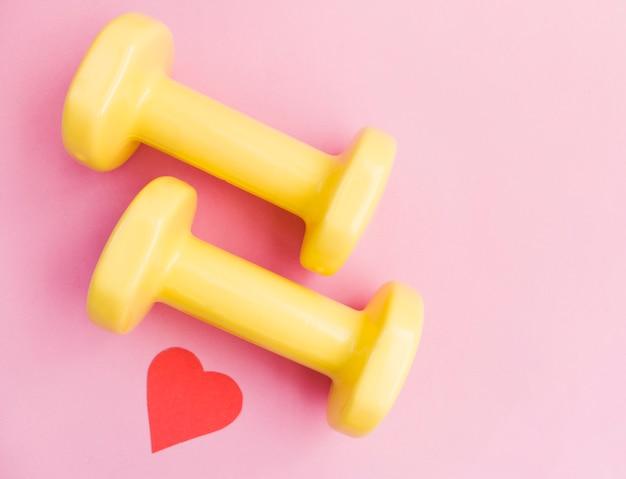Две желтые гантели и сердце на розовом фоне с копией пространства. концепция дня святого валентина, здоровый образ жизни, дарение подарков, любовь к спорту, шоппинг