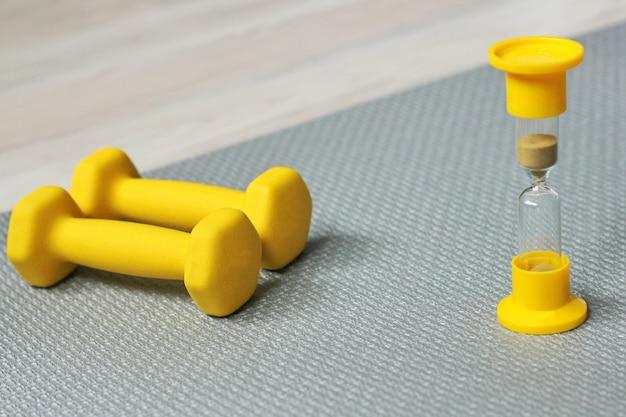 Две желтые гантели и желтые песочные часы рядом с ними на сером коврике для фитнеса. время заниматься спортом.