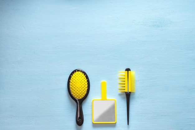 Two yellow hair comb crest brushes with handle for all types, and mirror isolated on blue copy space . minimalistic feminine flat lay
