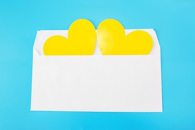 青い背景で隔離の白い封筒の2つの黄色いハート。閉じる。