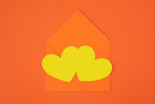 Two yellow hearts on orange envelope isolated on orange background