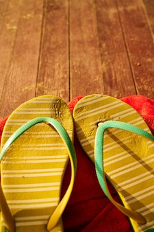 Two yellow sandals and a red towel on wood