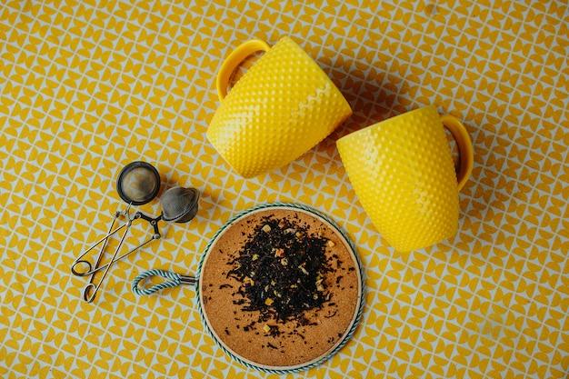 テーブルの上の2つの黄色いティーカップ。周りの葉茶、ティーカップ、テーブルの上にドライフラワーと黄色のテーブルの上の茶の染色器をメッシュします。