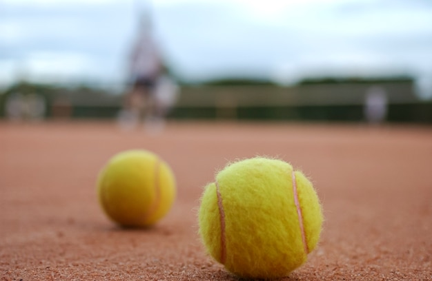 Two yellow tennis balls on the floor of the clay court
