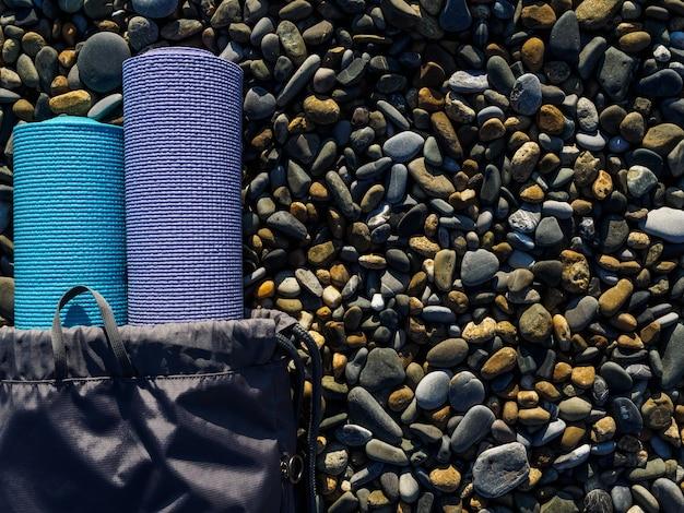 海の小石のクローズアップの2つのヨガマット