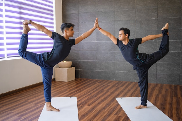Two yogis doing lord of dancers pose in gym